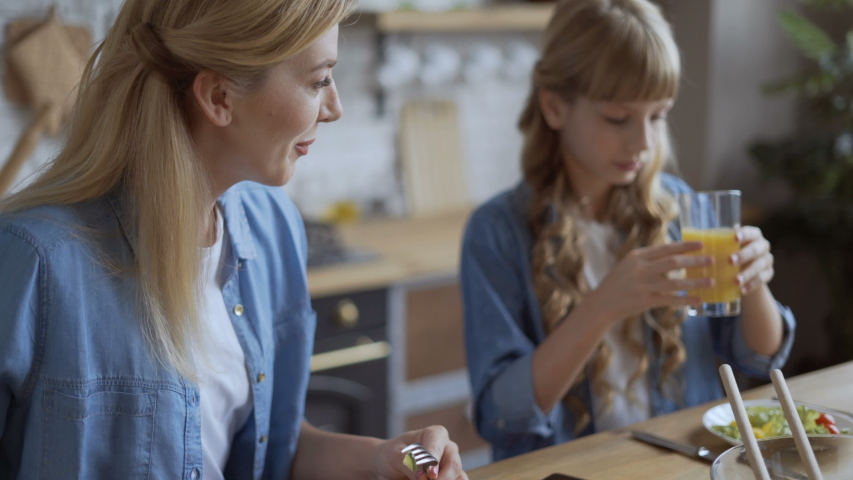 Girl shows mom funny video in mobile phone. Mom and daughter watch with a smartphone during lunch and have fun talking 4K | Shutterstock HD Video #1035559985