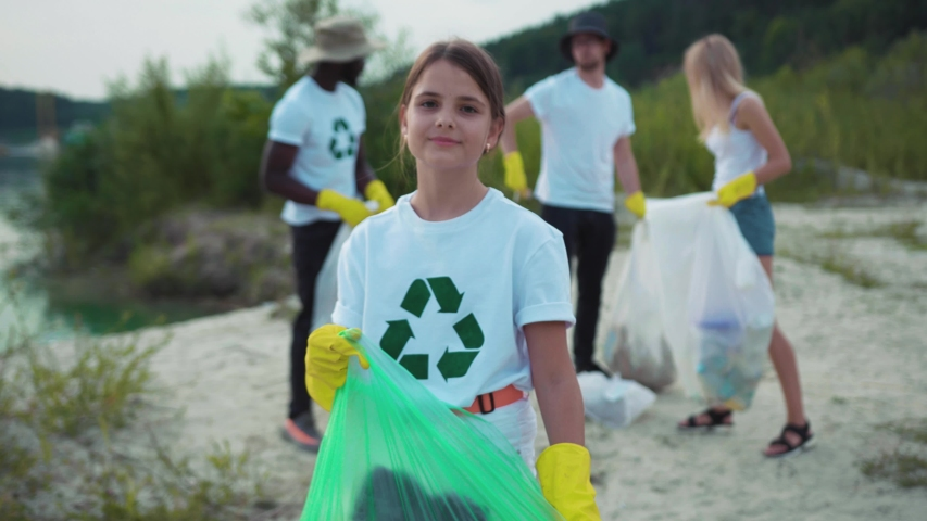 Adorable kid cleaning nature landscape from trash with environmental activists. Portrait of cute little girl volunteer smiling cleaning the beach. Save ecology. | Shutterstock HD Video #1035620045