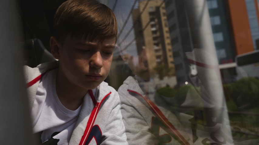 A young boy sitting in a subway car and looking out the window. Alone, tired and lost in thought. | Shutterstock HD Video #1035706535