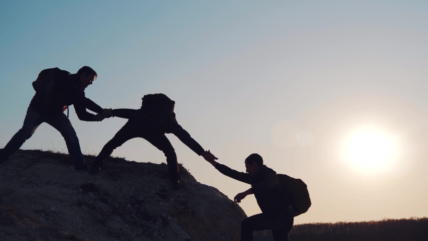 At sunset, tourists climb the mountain, overcoming obstacles. Silhouettes of men helping each other in a difficult situation. A friend, a young man, gives a helping hand. #1035706595