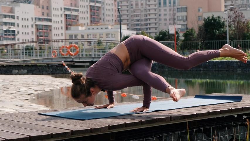 Young woman doing yoga exercises with city on background. eka pada kaundiniasana   Shutterstock HD Video #1035754835