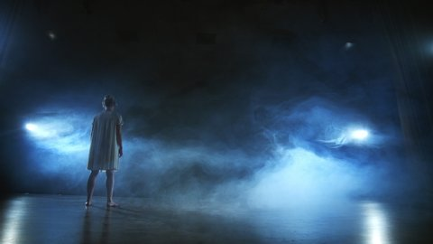 Woman in white dress on stage with smoke dancing modern ballet.