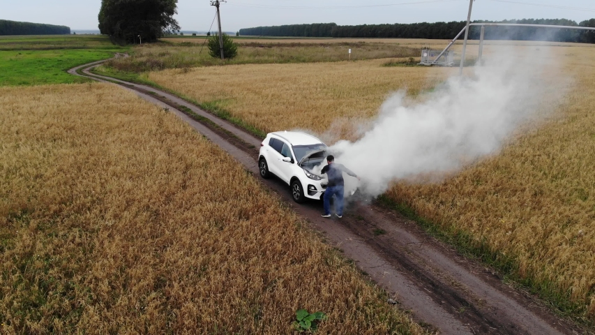 The car broke down, smokes from under the hood, the driver shocked. | Shutterstock HD Video #1035876185