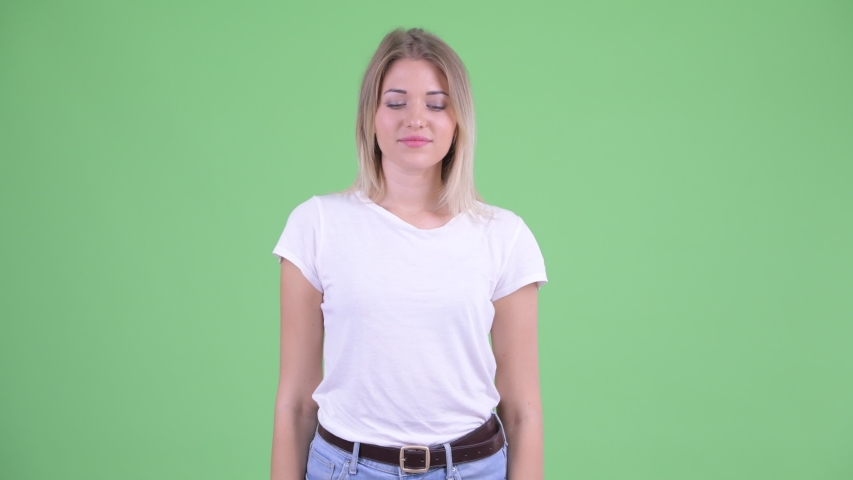Confused young blonde woman choosing between thumbs up and thumbs down   Shutterstock HD Video #1035920135