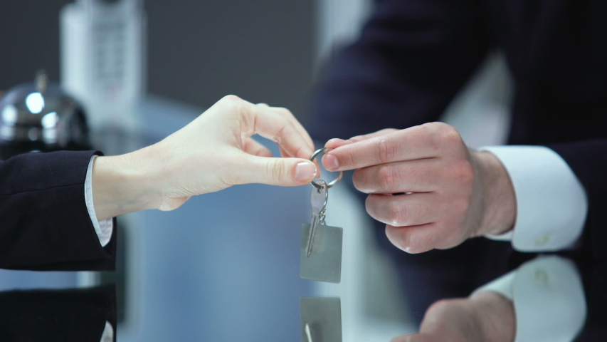 Male receptionist hand giving female visitor key on chain, service quality, trip | Shutterstock HD Video #1035929105