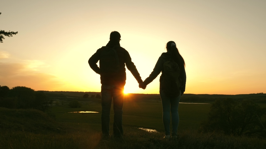 Travelers man and woman hold each other's hands and enjoy scenery at sunset. Lovers travelers travel with backpacks. Hiker Girl. Happy family of tourists on vacation travels. Romantic relationship. #1035969425