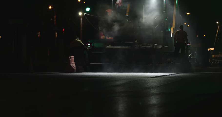 Worker operating asphalt paver machine during new road construction site. Rollers silhouette working at night city. Team of workers put asphalt on a town street. Steam rising from hot asphalt surface. | Shutterstock HD Video #1036004735