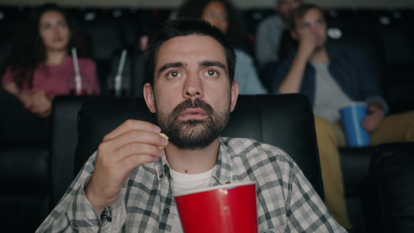 Slow motion of shocked young man watching film in cinema with open mouth dropping popcorn looking at screen with attention. People and reaction concept. | Shutterstock HD Video #1036058915