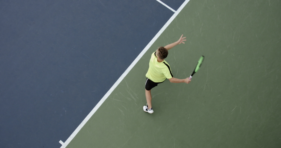 OVERHEAD CRANE Young Caucasian teenager male tennis player during a game or practice. Slow motion, 4K UHD RAW graded footage