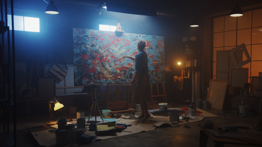 Talented Female Artist Works on Abstract Oil Painting, Using Paint Brush She Creates Modern Masterpiece. Dark and Messy Creative Studio where Large Canvas Stands on Easel Illuminated. Zoom out