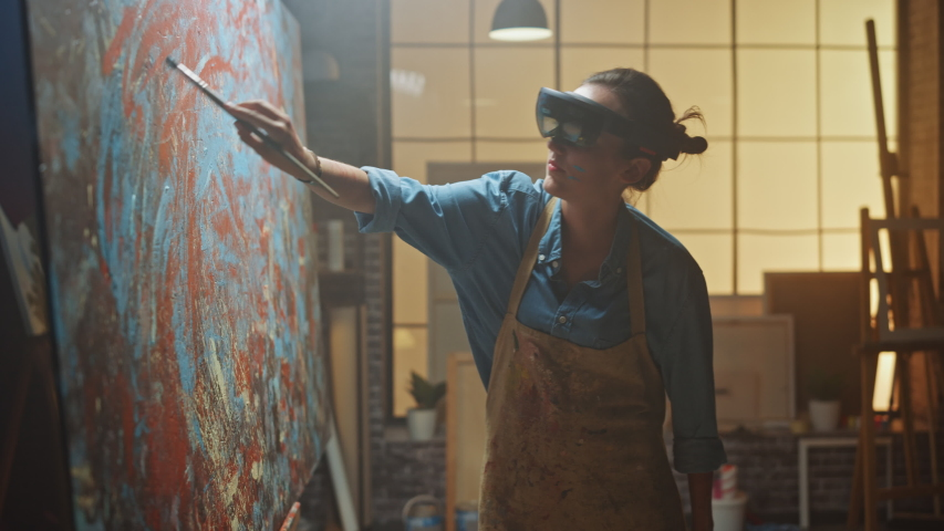 Talented Female Artist Wearing Augmented Reality Headset Working on Abstract Painting, Uses Paint Brush To Create New Concept Art Using Virtual Reality Interface. High tech Creative Modern Studio | Shutterstock HD Video #1036107635