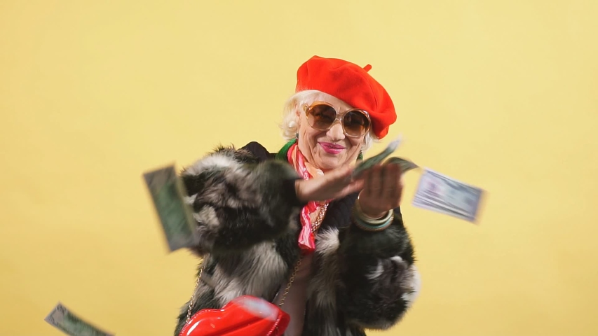 Rich elegant woman in fur coat and red cap throwing money, spending money on useless thing, isolated yellow background. studio shot