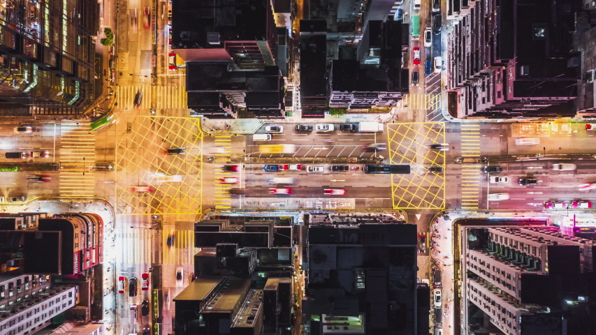 4K UHD Time-lapse of car traffic on road and people crossing street at night in Hong Kong downtown district, drone aerial top view. Commuter, Asia city life, or public transportation concept, Zoom out