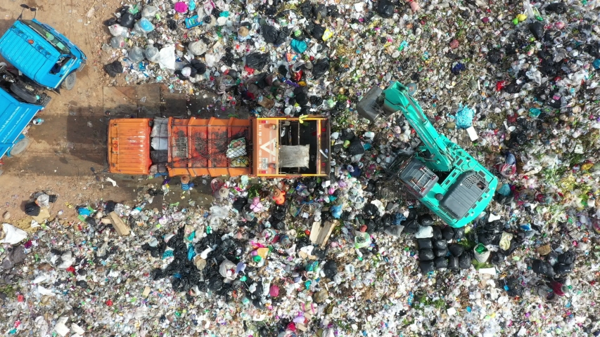 Garbage pile in trash dump or open landfill, Trash trucks dump waste products polluting in an trash dump, Surface and subsurface water contamination, modern hydraulic. Aerial top view | Shutterstock HD Video #1036275455