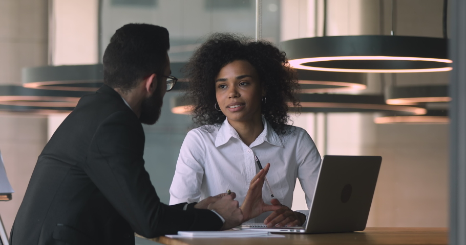 Female african manager broker advisor consulting arabic male client with laptop talking discussing bank loan deal benefits with arab customer collaborating convincing buy insurance services in office   Shutterstock HD Video #1036284905