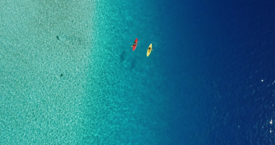 Wide aerial view of two kayakers paddling in a lagoon with pristine blue ocean water on a sunny sparkling day, amazing kayak adventures