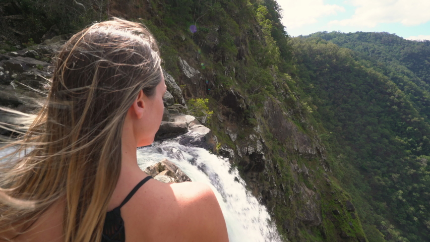 A tourist girl enjoy the amazing views from  an incredible waterfall. Filmed at Windin Falls Queensland. Australia. | Shutterstock HD Video #1036465805