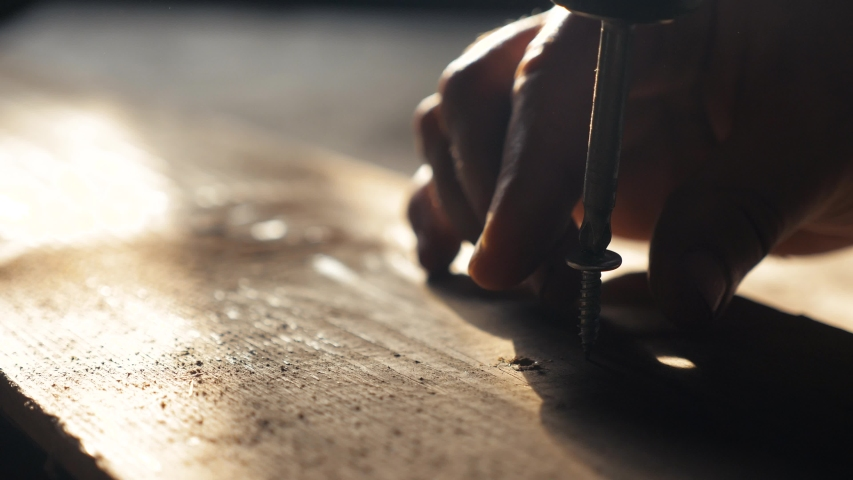 Man the worker tightens the screw with a screwdriver. Screws screwdriver twist in wooden board. Joinery lifestyle and construction work close up. screw out the screw | Shutterstock HD Video #1036527995