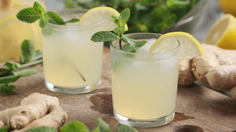 Delicious refreshing lemonade with ginger and mint in a transparent glass. Lemonade, ginger, mint leaves. Summer cocktail with mint and ginger. Ginger summer drink. Vitamin Summer Drink Concept 4K UHD