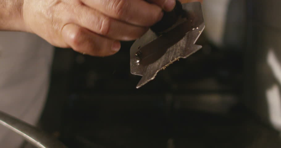 Super slow motion macro of a hand of middle aged chef grating black truffle in pan (close up)