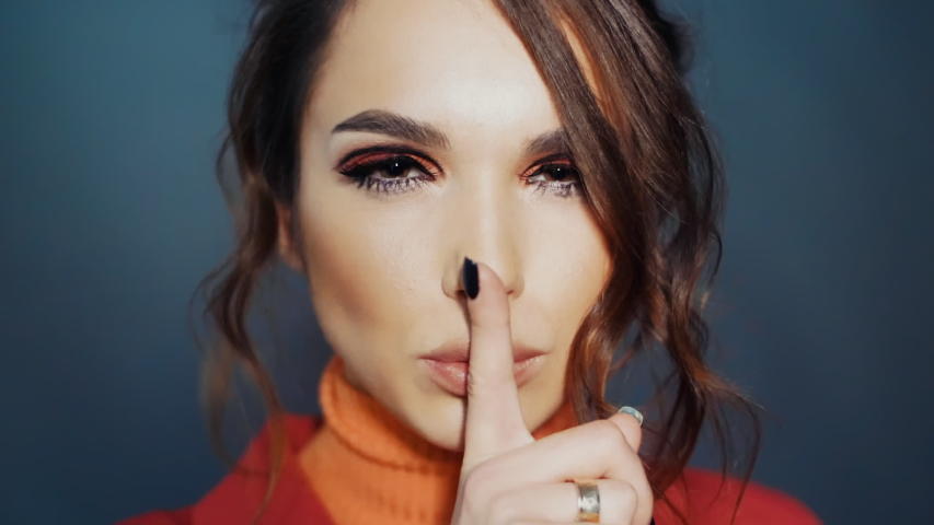 Pretty brunette making sign hush. Beautiful woman showing sign hush holding finger near lips. Sympathetic girl making hush gesture by forefinger. Young woman smiling coquettishly | Shutterstock HD Video #1036899725