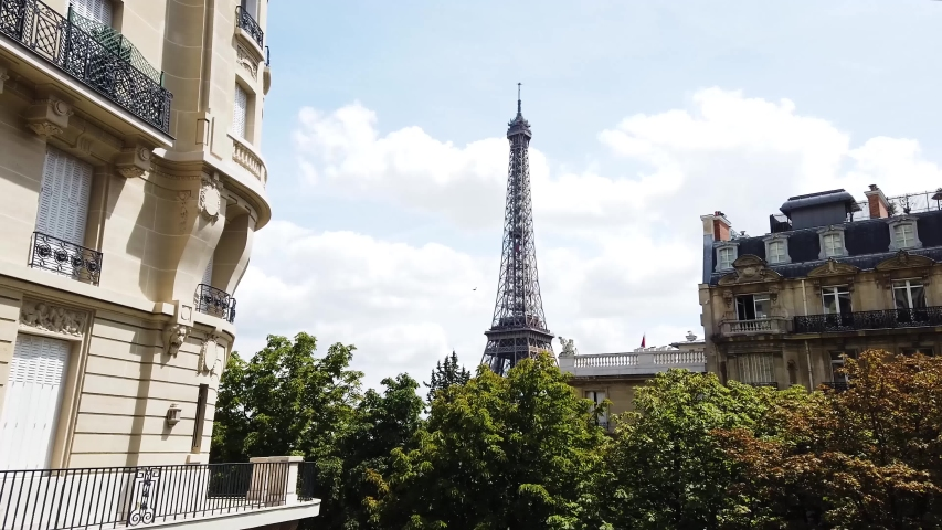 Cosy Paris street with view on the famous Eiffel Tower on a cloudy summer day, Paris France | Shutterstock HD Video #1036917365