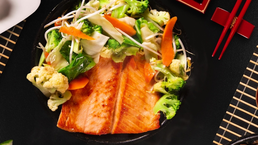 Delicious Teppanyaki Salmon grill food with vegetable in the iron pan with smoke. Top view.   Shutterstock HD Video #1036926995