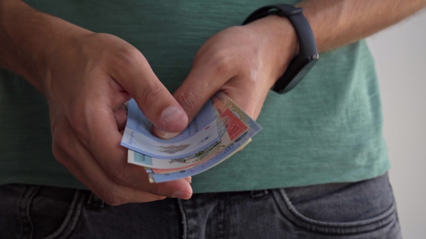A man shows banknotes of different countries. | Shutterstock HD Video #1036981145