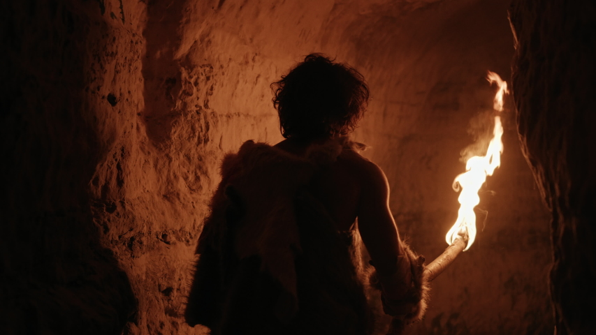 Primeval Caveman Wearing Animal Skin Exploring Cave At Night, Holding Torch with Fire Looking at Drawings on the Walls at Night. Neanderthal Searching Safe Place to Spend the Night.Back View Following | Shutterstock HD Video #1037019395