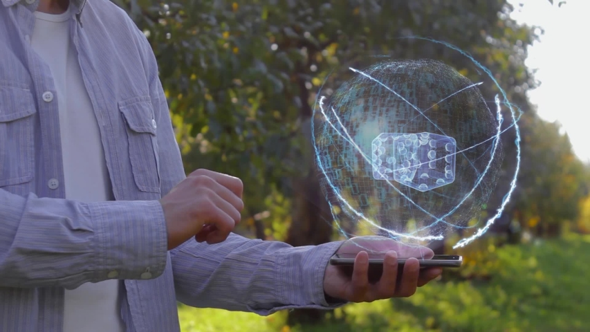 Unrecognizable man shows conceptual hologram with dices. Farmer on the background of the apple orchard in casual clothes with the technology of the future mobile screen | Shutterstock HD Video #1037038565