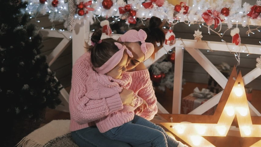 Happy mother having fun with her kid daughter near Christmas tree. Beautiful mother and daughter in pink pullovers. Mother tickling her little daughter in slow motion. Motherhood concept. Medium shot