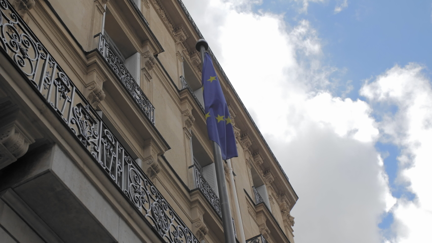 Flag of the European Union on the background of a typical French house in Paris. In the frame of the blue sky and white clouds. Slow Motion. | Shutterstock HD Video #1037140145