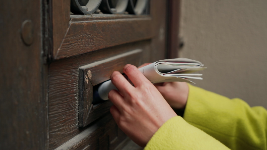 Postman puts a letter or newspaper or magazine in the mailbox at the door of a residential building or a person puts a brochure with advertising. Close-up | Shutterstock HD Video #1037142755