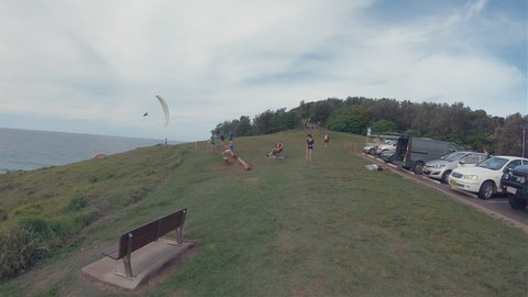 PAT MORTON LOOKOUT,AUSTRALIA - APRIL 8, 2019: Paragliders Paragliding.People Watching Para Gliders Flying High In Windy Sky At Lennox Head Coastline on Headland Hills.Popular Outdoor Leisure Activity.