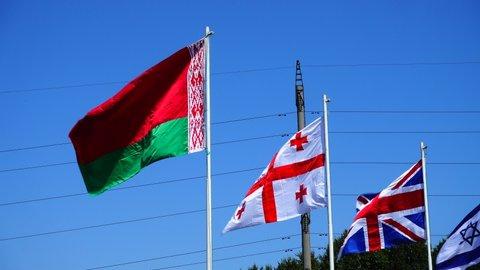 Flags of Belarus, Georgia, Great Britain and Israel on flagpoles.