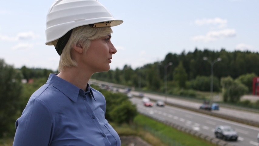Young blonde woman with construction helmet outdoors is smiling at the camera. Cars driving on the road in the background.Close Up Shot | Shutterstock HD Video #1037212025