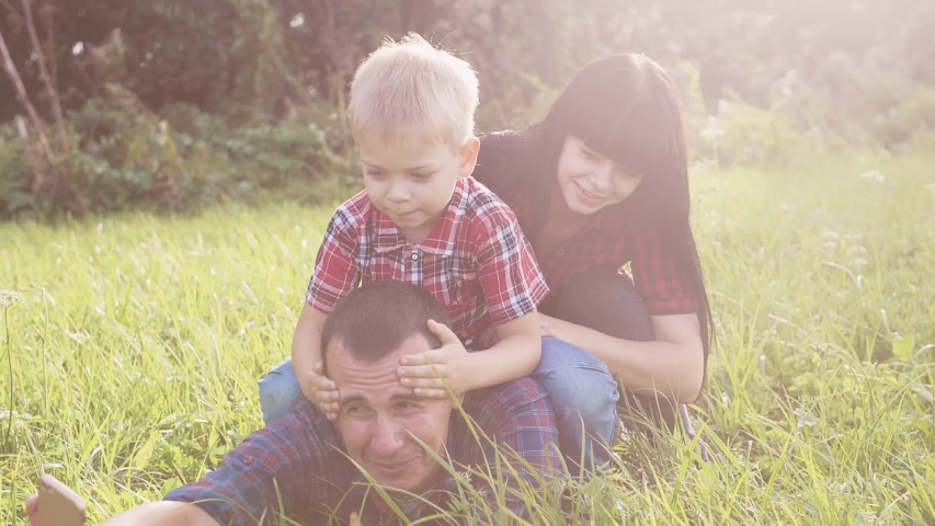 Happy family teamwork outdoors have fun concept outdoors slow motion video. mom dad and son take a photo with a smartphone in nature are sitting on the grass have fun playing. mom girl dad man and son   Shutterstock HD Video #1037217995