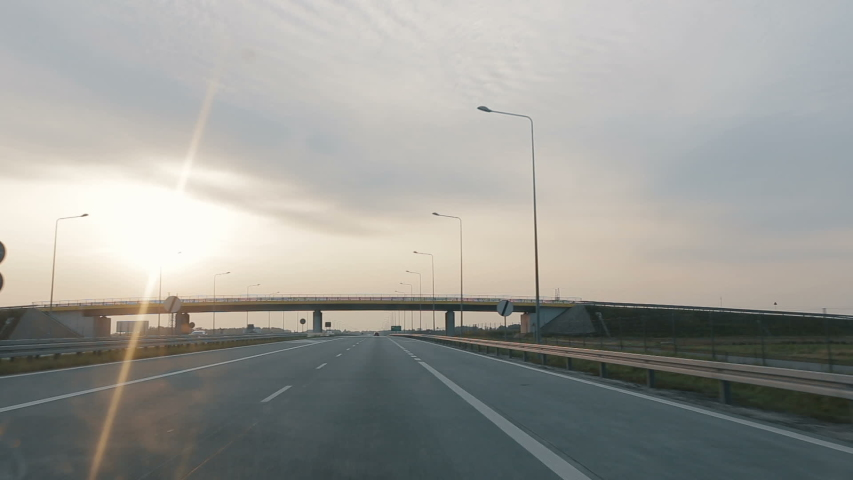 POV driving along a wide empty morning road early in the morning during sunrise.. Point of view driving, view from inside the car on on the autobahn in Poland. | Shutterstock HD Video #1037223665