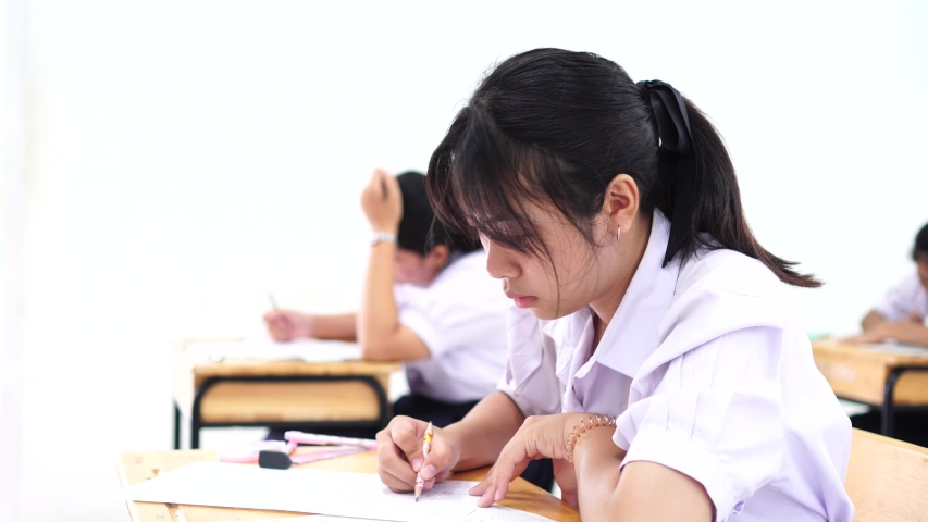 Exam assessment concept, Asian students young girls in college or high school having test exams for taking writing examination in school rows chairs at classroom with uniform educational of Thailand. | Shutterstock HD Video #1037268215