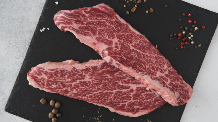 Fresh raw beef meat Denver Steak with peppercorns, seasonings and spices, ready to grill, rotating 360. Top view | Shutterstock HD Video #1037280695