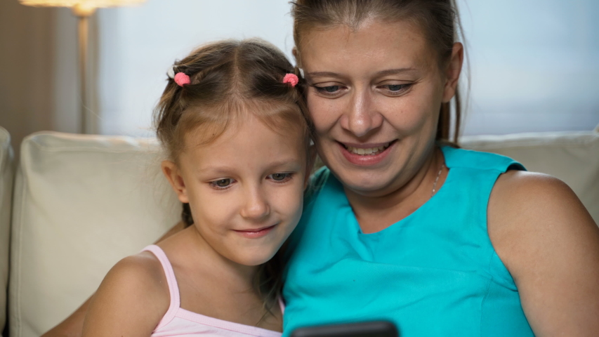 Little Girl Child With Mother Home On Sofa Using Smartphone   Shutterstock HD Video #1037314505