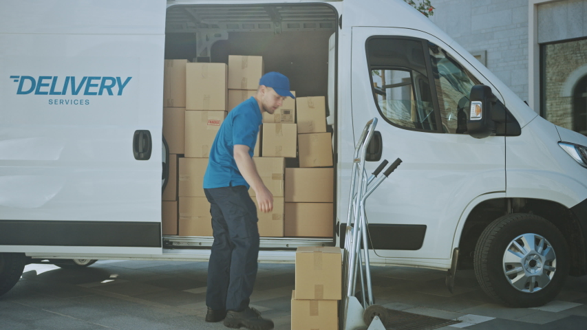 Delivery Man Uses Hand Truck Trolley Full of Cardboard Boxes and Packages, Loads Parcels into Truck / Van. Professional Courier / Loader helping you Move, Delivering Your Purchased Items Efficiently | Shutterstock HD Video #1037351195
