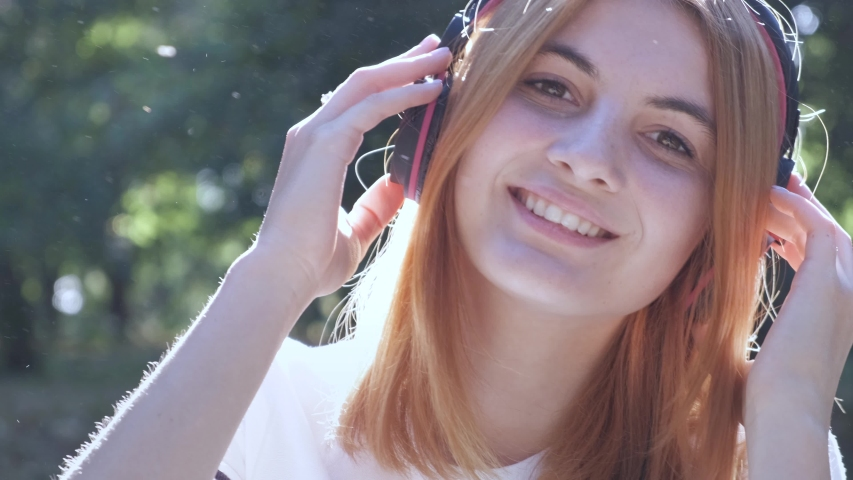 Pretty teenage girl with red hair listening to music in earphones outdoors in summer park.   Shutterstock HD Video #1037355395