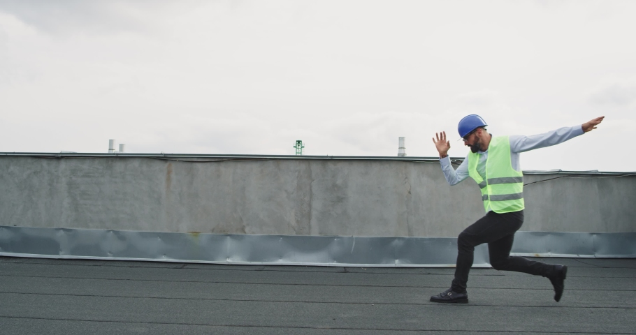 Attractive man with a safety helmet on the rooftop of construction site engineer or architect dancing excited in the middle of working day | Shutterstock HD Video #1037504405
