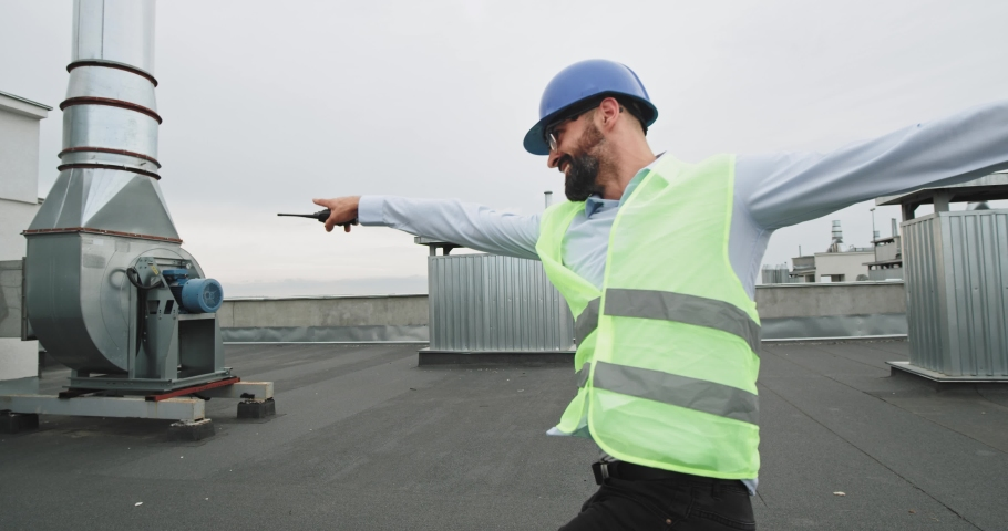 In front of the camera beautiful smiling architect man dancing excited on the rooftop of construction site wearing a helmet and holding the ration | Shutterstock HD Video #1037504435