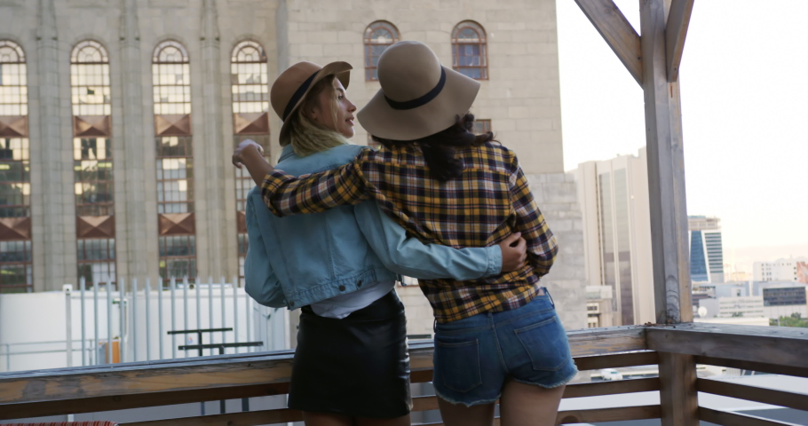 Rear view of a happy young Caucasian and mixed race female friends enjoying themselves at a party on a rooftop, embracing and admiring the view, with a building in the background   Shutterstock HD Video #1037549585
