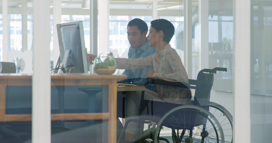 Side view of young Caucasian female business creative in a wheelchair and a young Caucasian male business creative working in a modern office, using a computer and discussing | Shutterstock HD Video #1037569715