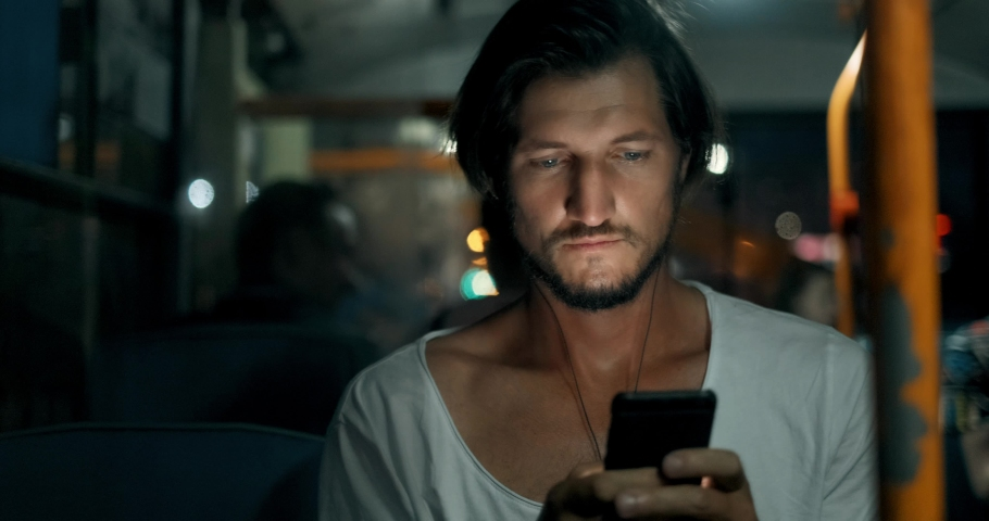 Young man holds smartphone and smiling while traveling by bus at night. Bearded male in headphones with phone, touches screen with fingers and looks out window | Shutterstock HD Video #1037816945