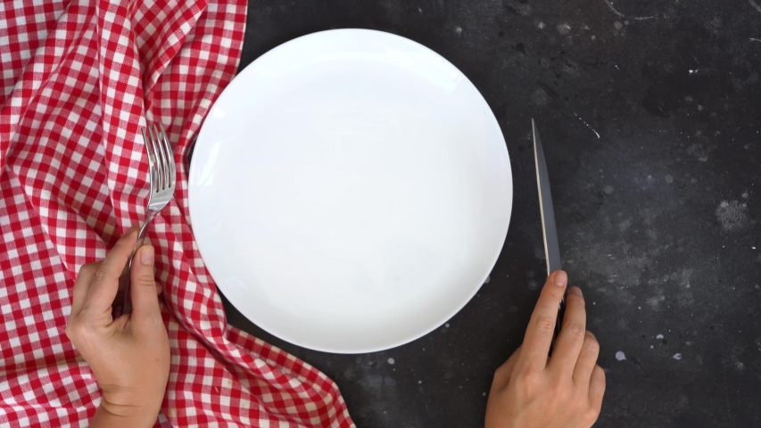 Abstract food background - empty white plate with red napkin and cutlery over black table, hands holding fork and knife | Shutterstock HD Video #1037888465