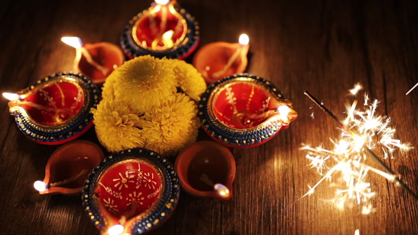 Colorful Diwali oil lamps, Deepavali oil lamps lighted in beautiful formation with flowers in middle. Oil lamps with sparkler. Motion of igniting hand held sparkler / crackers   | Shutterstock HD Video #1037941205